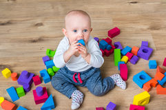 Cute little baby girl playing with colorful toy blocks. On the floor Stock Image