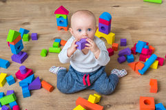 Cute little baby girl playing with colorful toy blocks. On the floor Royalty Free Stock Photo