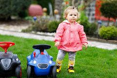 Cute little baby girl playing with two toy cars in garden. Adorable toddler child having fun. Girl in colorful fashion Royalty Free Stock Photos