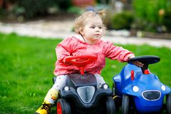 Cute little baby girl playing with two toy cars in garden. Adorable toddler child having fun. Girl in colorful fashion Royalty Free Stock Photography