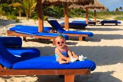 Cute little baby girl with seashells on tropical beach Royalty Free Stock Photos