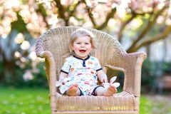 Cute little baby girl sitting on big chair in garden. Beautiful happy smiling toddler with blooming pink magnolia tree. On background. Healthy child enjoying stock image