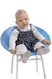 Cute little baby girl sitting in a chair Royalty Free Stock Photos