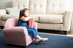 Baby girl enjoying watching tv a home. Cute little baby girl sitting on couch in living room with popcorn and watching television Stock Photo