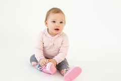 Cute little baby girl sitting on floor isolated Royalty Free Stock Photography