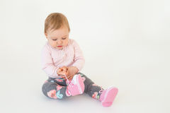 Cute little baby girl sitting on floor isolated Stock Images