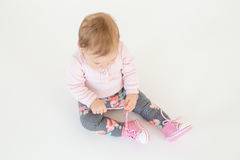 Cute little baby girl sitting on floor isolated Royalty Free Stock Image