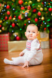 Cute little baby girl sitting in front of Christmas tree Royalty Free Stock Image
