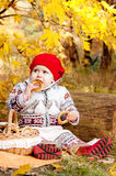 Cute little baby girl sitting on rug in the woods. Royalty Free Stock Image