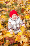 Cute little baby girl sitting on rug in the woods. Stock Image