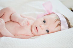 Cute little baby girl on white blanket staring up Royalty Free Stock Photo