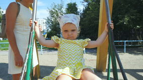 Cute little baby girl is swinging stock footage