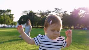 Cute Little baby girl walks by grass stock footage