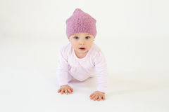 Cute little baby girl wearing hat sitting on floor. Photo of cute little baby girl wearing hat sitting on floor isolated over white background. Looking at camera Stock Image