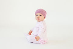 Cute little baby girl wearing hat sitting on floor. Photo of cute little baby girl wearing hat sitting on floor isolated over white background. Looking at camera Royalty Free Stock Images