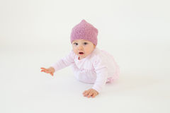 Cute little baby girl wearing hat sitting on floor. Photo of cute little baby girl wearing hat sitting on floor isolated over white background. Looking at camera Royalty Free Stock Photography