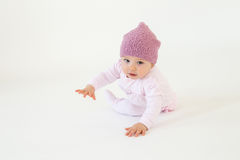 Cute little baby girl wearing hat sitting on floor. Photo of cute little baby girl wearing hat sitting on floor isolated over white background. Looking at camera Stock Photography
