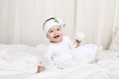 Cute little baby girl in white clothes, sitting on bed, playing with toy Stock Photography