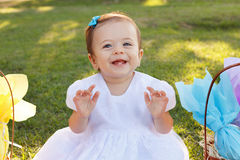 Cute little baby girl in white dress near wicker basket with gif Royalty Free Stock Photos
