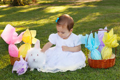Cute little baby girl in white dress touching rabbit, Easter cho Stock Photography