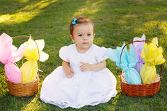 Cute little baby girl with wicker basket with chocolate eggs Stock Photo