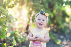 Cute little baby girl in yellow dress standing in the field of g Royalty Free Stock Photo