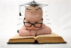 Cute little baby in glasses with painted professor hat. Lieing on old book on light background royalty free stock image