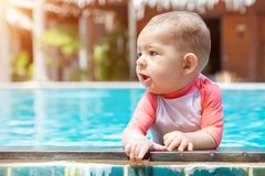 A cute little baby holds to the edge of the tropical pool and looks to the left. Infant girl swim at summer vacation.  stock image
