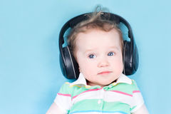 Cute little baby with huge earphones Stock Images