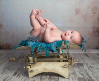 Cute little baby with legs up on scales Stock Image