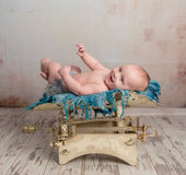 Cute little baby with legs up on scales Royalty Free Stock Photos