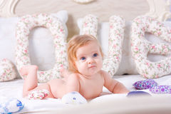 Cute little baby lies down on the bed Stock Photography