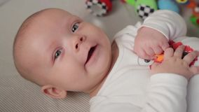 A cute little baby is looking into the camera and is happy on a white bed sheet. stock footage