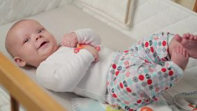 A cute little baby is looking into the camera and is happy on a white bed sheet. stock video