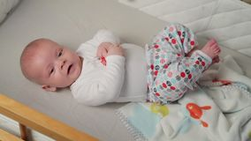 A cute little baby is looking into the camera and is happy on a white bed sheet. stock video footage