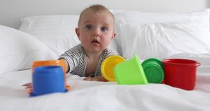 Funny baby with toys on bed. Cute little baby looking up while lying on comfortable bed near colorful toy buckets stock video footage