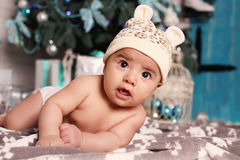 Cute little baby  lying beside Christmas tree with a lot of presents Stock Photography