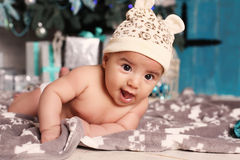 Cute little baby  lying beside Christmas tree with a lot of presents Royalty Free Stock Photography
