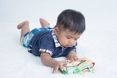 Cute little baby lying on soft blanket and reading book stock images