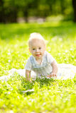 Cute little baby in the park on the grass. Sweet baby outdoors. Stock Photography