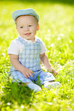 Cute little baby in the park on the grass. Sweet baby outdoors. Royalty Free Stock Images