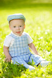 Cute little baby in the park on the grass. Sweet baby outdoors. Stock Image