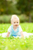 Cute little baby in the park on the grass. Sweet baby outdoors. Stock Images