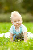 Cute little baby in the park on the grass. Sweet baby outdoors. Stock Photos