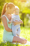 Cute little baby in the park with mother on the grass. Sweet bab Stock Images