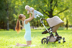 Cute little baby in the park with mother on the grass. Sweet baby and mom outdoors. Smiling emotional kid with mum on a walk. Sm. Cute little baby in summer park royalty free stock photos