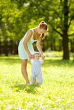 Cute little baby in the park with mother on the grass. Sweet baby and mom outdoors. Smiling emotional kid with mum on a walk. Sm. Cute little baby in summer park royalty free stock photography