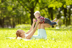 Cute little baby in the park with mother on the grass. Sweet baby and mom outdoors. Smiling emotional kid with mum on a walk. Sm. Cute little baby in summer park stock photo