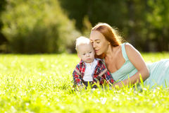 Cute little baby in the park with mother on the grass. Sweet bab Stock Photo