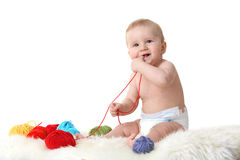 Cute little baby playing with balls of wool stock images